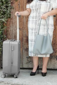 Femme de grande taille en robe debout à la porte en bois de l'hôtel massif avec valise et sac en cuir à la main