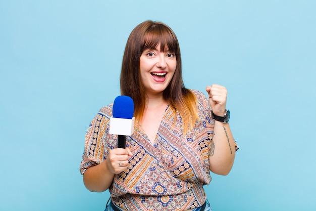 Femme grande taille se sentant choquée, excitée et heureuse, riant et célébrant le succès, disant wow!