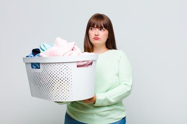 Femme grande taille se sentant triste, bouleversée ou en colère et regardant sur le côté avec une attitude négative, fronçant les sourcils en désaccord