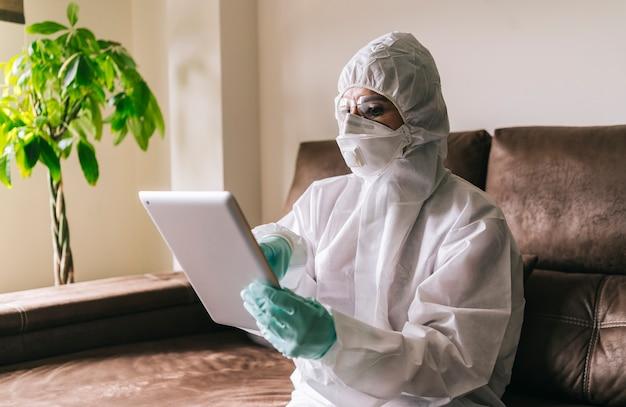 Une femme avec de grandes mesures de sécurité contre un virus travaille à domicile