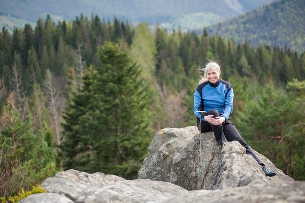Femme grimpante au sommet du rocher
