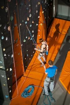 Femme grimpante grimpe sur un mur d'escalade intérieur