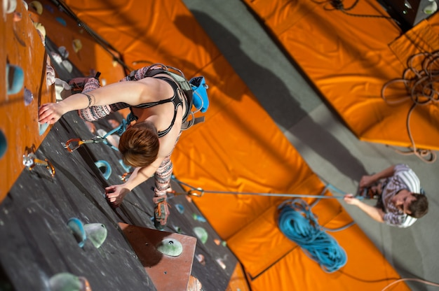 Femme grimpe avec des carabines et une corde