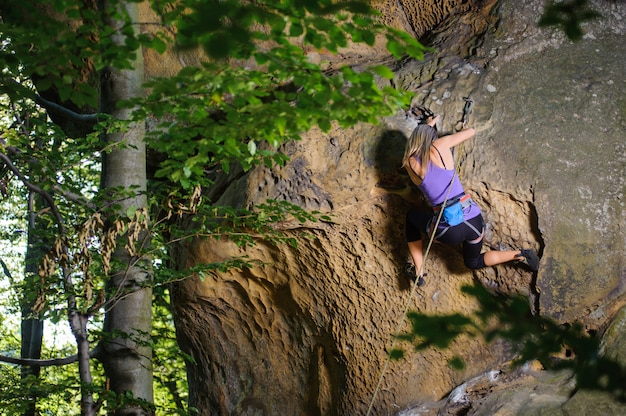 Femme, grimpeur, escalade, à, corde, sur, a, mur rocheux