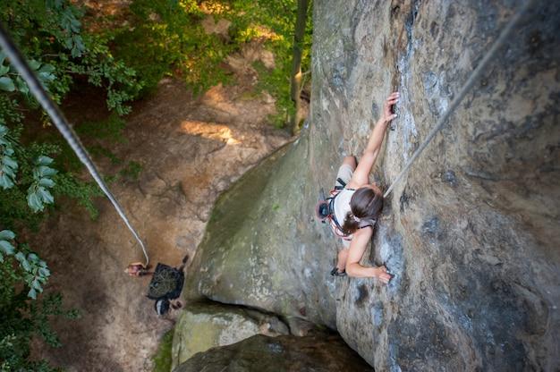 Femme grimpeur grimpe sur un mur rocheux