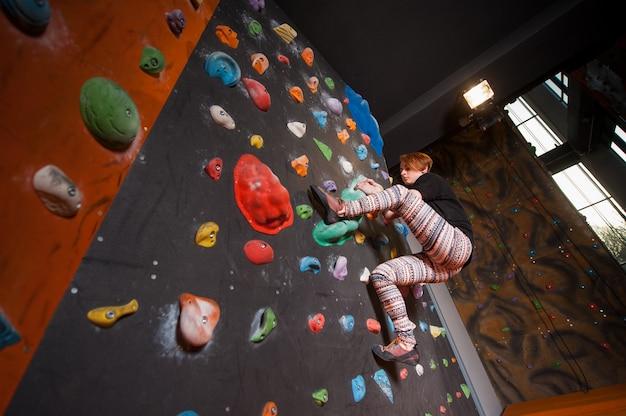 Femme grimpeuse sur mur artificiel d'escalade intérieure atteint le sommet. bloc