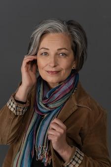 Femme grisonnante élégante sourit avec charme en regardant la caméra. beauté caucasienne d'âge moyen vêtue d'une veste en velours côtelé marron avec une écharpe multicolore touche son visage avec la main. concept de soins de la peau anti-âge
