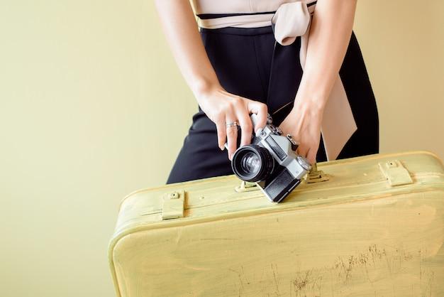Femme avec de gros bagages court à l'aéroport.vacances chaudes, voyagez dans des pays chauds sur la mer. fille avec de grandes valises jaunes sur fond jaune, tenant un chapeau de paille, une femme élégante tropicale