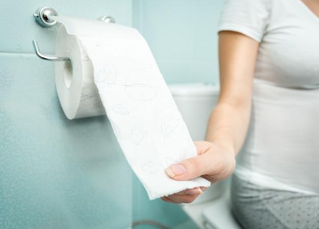 Femme en gros plan assise sur les toilettes et utilisant du papier toilette
