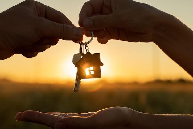 Une femme en gros plan donne à un homme la clé d'une nouvelle maison sur fond d'un beau coucher de soleil le concept...