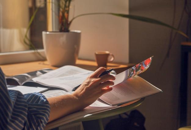 Femme en gros plan lisant des livres se préparant à l'examen tournant des pages étudiant avec un manuel académique