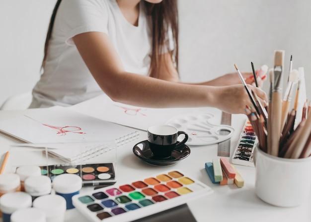 Femme en gros plan avec des objets de peinture