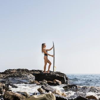 Femme avec grosse planche de surf au bord de mer rocheuse
