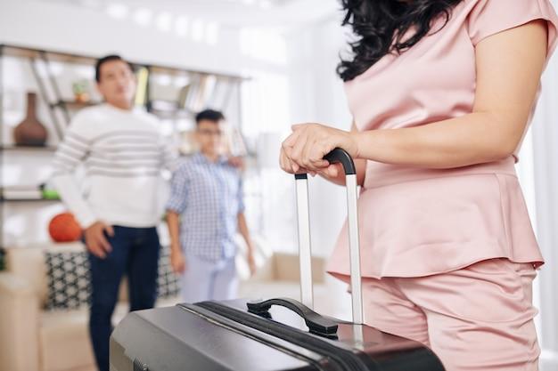 Femme avec grosse valise quittant la maison pour un voyage d'affaires, son mari et son fils restant à la maison