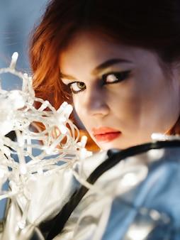 Femme avec une guirlande de maquillage lumineux près de la mode du visage posant en gros plan