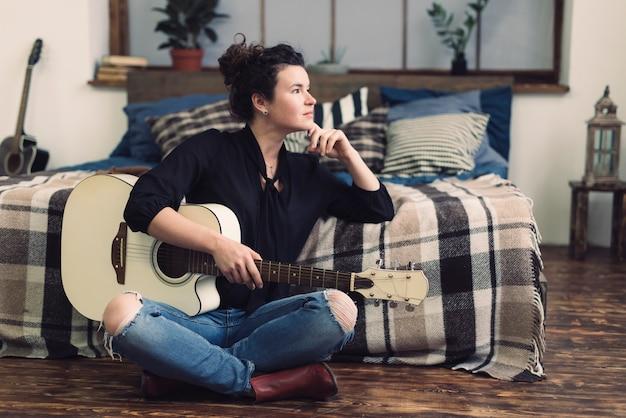 Femme à la guitare assis devant le lit