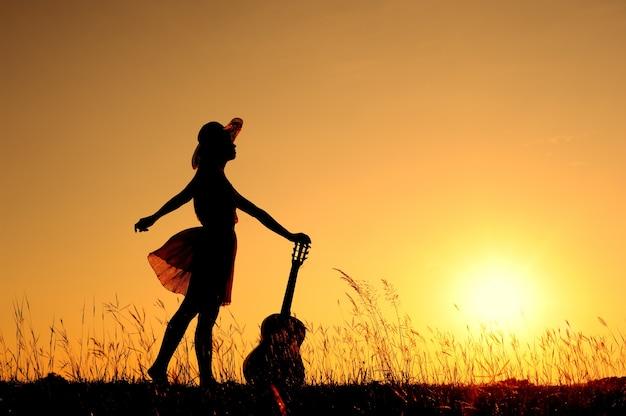 Femme et guitare avec la silhouette du coucher du soleil