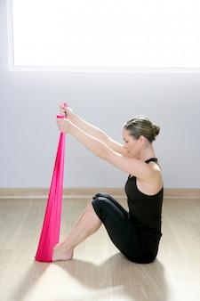 Femme de gym pilates yoga bande de résistance caoutchouc rouge