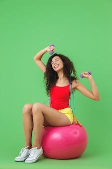 Femme gymnastique portant des vêtements d'été soulevant des haltères alors qu'elle était assise sur un ballon de fitness pendant l'aérobic contre le mur vert