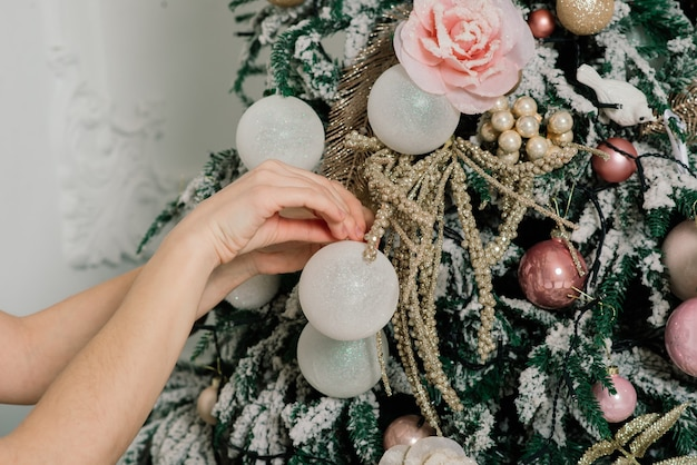 Femme habillant l'arbre de noël, souriant, s'asseyant dans l'intérieur de nouvelle année