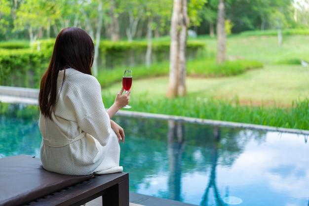 Femme habillé peignoir assis sur une chaise longue dans la piscine