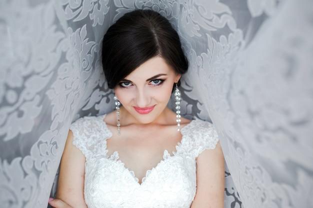 Femme habillée comme une jeune mariée appuyée contre un mur