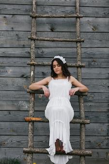 Femme habillée comme une jeune mariée monter un escalier en bois