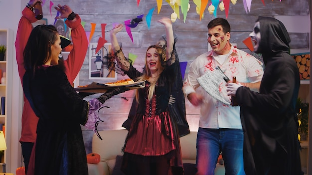 Femme habillée comme une sorcière arrivant avec une pizza à la fête d'halloween pour ses amis.