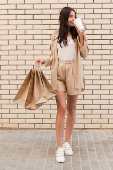 Femme habillée élégante, boire du café et tenant des sacs