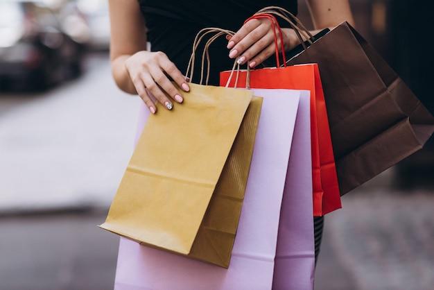 La femme habillée à la mode détient des sacs à provisions colorés dans la rue, concept d'achat