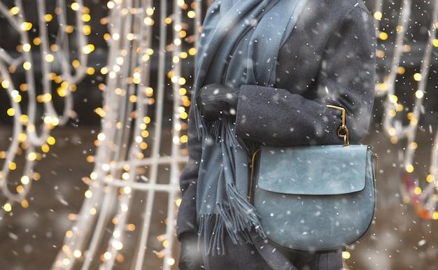 Une femme habillée à la mode porte un manteau gris et une écharpe tenant un sac à main en cuir bleu marchant pendant les chutes de neige