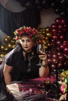 Femme habillée en sorcière avec des fleurs sur la tête