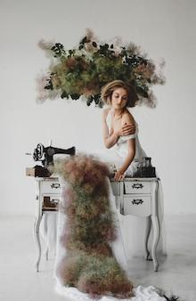Femme en habits blancs assise dans une pièce avec des fleurs et une machine à coudre