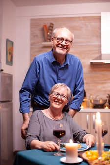Femme handicapée excitée en fauteuil roulant et son mari derrière elle en regardant la caméra. joyeux couple de personnes âgées gai dînant ensemble dans la cuisine confortable, appréciant le repas, célébrant leur anniversaire
