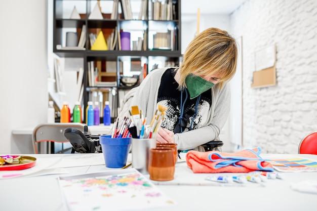 Femme handicapée en fauteuil roulant apprenant à peindre dans une académie de dessin