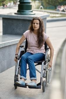 Une femme handicapée en fauteuil roulant monte la rampe
