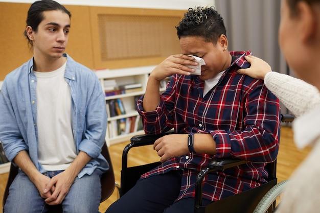 Femme handicapée pleurant en groupe de soutien