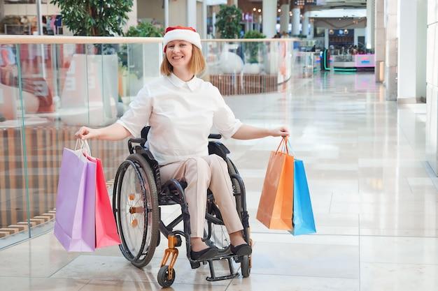 Une femme handicapée portant un bonnet de noel, bénéficiant d'une vente de noël dans un centre commercial