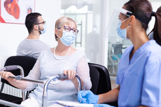 Femme handicapée regardant le personnel médical dans la salle d'attente de l'hôpital tenant un cadre de marche portant une protection contre le coronavirus. patient et personnel médical dans la clinique. docteur en salle d'examen.