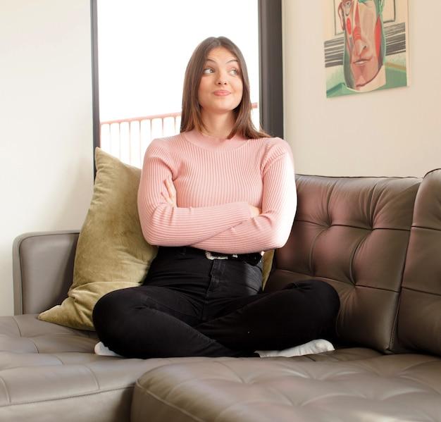 Femme haussant les épaules, se sentant confuse et incertaine, doutant des bras croisés et regard perplexe