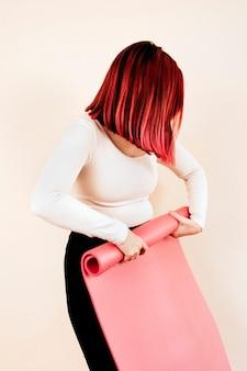 Femme en haut à manches longues roulant tapis de yoga rose tourné en studio