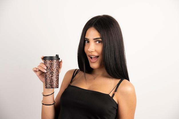 Femme en haut noir tenant une tasse de café avec une expression heureuse. photo de haute qualité
