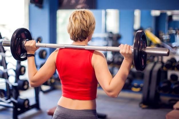 Femme en haut rouge aux cheveux blonds courts se préparant à faire des squats en salle de sport. concept de personnes, de remise en forme et de style de vie