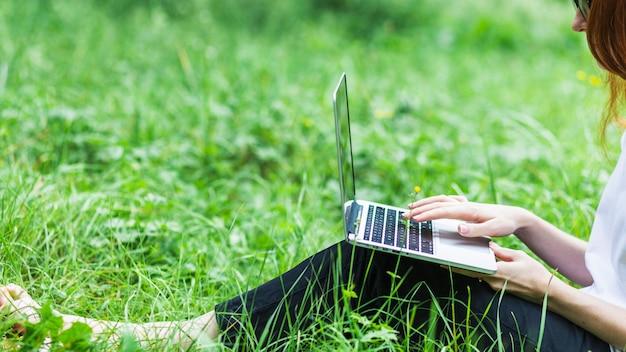 Femme sur l'herbe avec un ordinateur portable