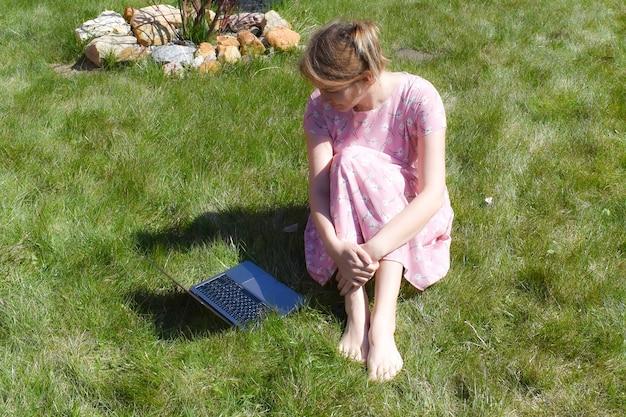 Femme sur l'herbe verte avec ordinateur portable