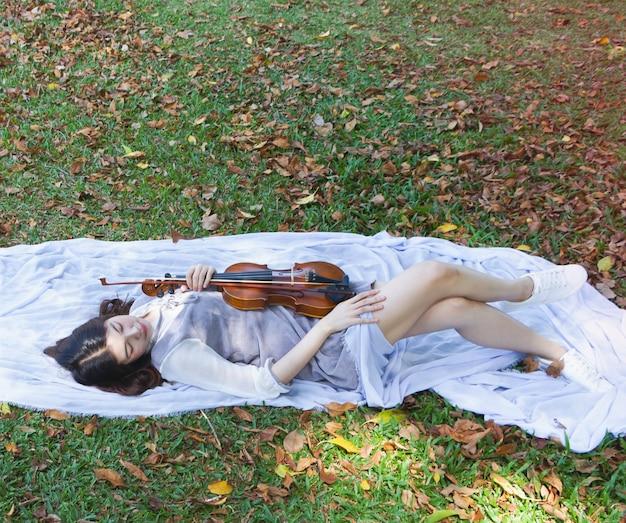 Femme, sur, herbe verte, rez-de-chaussée, tenue, violon, main