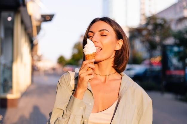 Femme à l'heure du coucher du soleil d'été ayant un cornet de crème glacée dans la rue de la ville