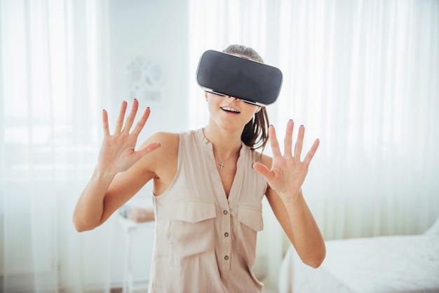 Une femme heureuse acquiert de l'expérience en utilisant un casque de réalité virtuelle avec des lunettes vr dans un environnement lumineux