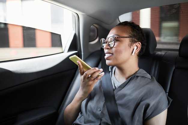 Femme heureuse africaine assise sur le siège arrière de la voiture, parlant au téléphone portable et souriant
