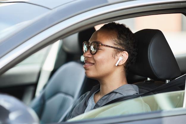 Femme heureuse africaine dans des écouteurs sans fil conduisant par sa voiture